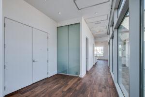 Double door entry into hallway with glass floor to ceiling windows