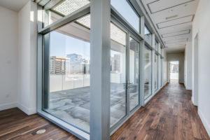 Floor to ceiling glass walls in the hallway overlooking terrace