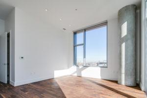 A large window near a cement pillar